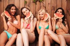 4 молодых милых смешных девушки есть арбуз Стоковое Изображение RF
