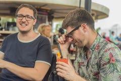 2 молодых мужских друз имея потеху, выпивая коктеили и беседуя с друзьями на кафе террасы в городке Стоковая Фотография RF