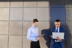 2 молодых мужских люд, бизнесмен, студенты держат компьтер-книжку и таблетку Стоковая Фотография
