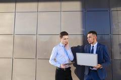 2 молодых мужских люд, бизнесмен, студенты держат компьтер-книжку и таблетку Стоковые Изображения RF
