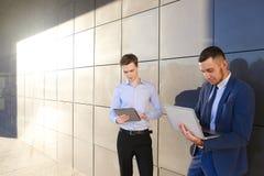 2 молодых мужских люд, бизнесмен, студенты держат компьтер-книжку и таблетку Стоковое фото RF