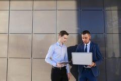 2 молодых мужских люд, бизнесмен, студенты держат компьтер-книжку и таблетку Стоковое Изображение RF