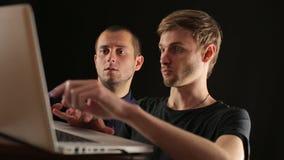 2 молодых обсуждая бизнесмена с портативным компьютером видеоматериал