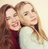 2 молодых подруги в свитерах зимы внутри помещения имея потеху lifestyle Белокурые предназначенные для подростков друзья закрываю стоковые фото