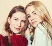 2 молодых подруги в свитерах зимы внутри помещения имея потеху lifestyle Белокурые предназначенные для подростков друзья закрываю стоковое фото