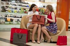 2 молодых подруги сидя в магазине и ослабляют после shoppi Стоковая Фотография