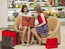 2 молодых подруги сидя в магазине и ослабляют после shoppi Стоковое фото RF