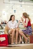 2 молодых подруги сидя в магазине и ослабляют после shoppi Стоковые Фото