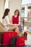 2 молодых подруги сидя в магазине и ослабляют после shoppi Стоковое Фото