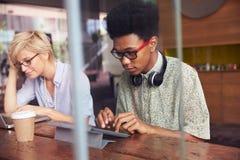 2 молодых предпринимателя работая на компьтер-книжке в кофейне Стоковые Изображения