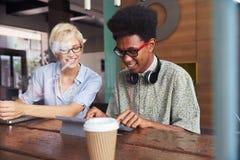 2 молодых предпринимателя работая на компьтер-книжке в кофейне Стоковое фото RF