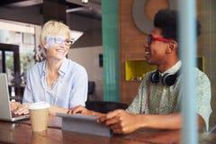2 молодых предпринимателя работая на компьтер-книжке в кофейне Стоковая Фотография RF