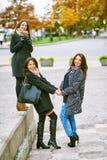 3 молодых привлекательных девушки имея потеху фотографируя совместно на прогулке города Образ жизни Стоковая Фотография