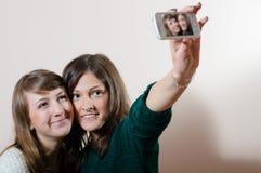 2 молодых привлекательных прелестных камеры женщин счастливых усмехаться & смотреть имея обнимая потехи дружелюбное и делая selfi Стоковое фото RF