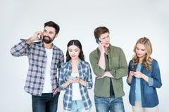4 молодых друз в вскользь одеждах используя smartphones Стоковое Фото