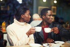 2 молодых друз держа чашки выпивают кофе в кафе Стоковое фото RF