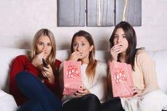 3 молодых друз есть попкорн и смотря кино Стоковые Изображения