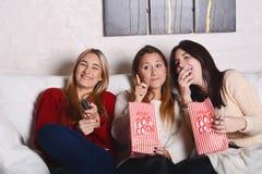 3 молодых друз есть попкорн и смотря кино Стоковая Фотография RF