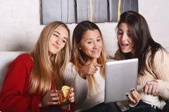 3 молодых друз имея потеху и используя таблетку Стоковая Фотография