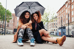 2 молодых друз сидя на скейтборде с зонтиком Стоковые Изображения