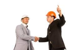 2 молодых сердитых мужских инженера тряся руки Стоковые Изображения