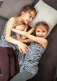 2 молодых сестры нажимая один другого на кровати Стоковые Изображения RF