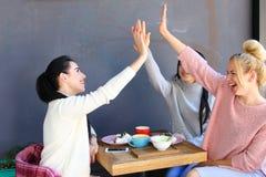 3 молодых симпатичных подруги девушек тараторят, радуются, высоко 5 Стоковая Фотография