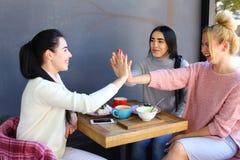 3 молодых симпатичных подруги девушек тараторят, радуются, высоко 5 Стоковая Фотография RF