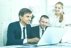 3 молодых сотрудника работая в офисе компании стоковое фото rf