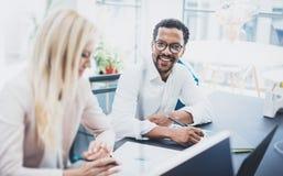 2 молодых сотрудника работая совместно в современном офисе Стекла чернокожего человека нося, смотрящ камеру и усмехаться Стоковое фото RF