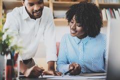 2 молодых сотрудника работая совместно в современном офисе Черные бизнесмены обсуждая новый startup проект горизонтально Стоковая Фотография