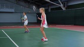 2 молодых спортсмена в рекреационной зоне играя игру спорта Счастливая сестра и брат имея урок тенниса тратя время на акции видеоматериалы