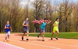 4 молодых спринтера развевая американский флаг на следе Стоковое Фото
