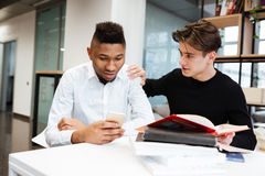 2 молодых студента в библиотеке выбирают между книгой и мобильным телефоном Стоковые Изображения