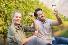2 молодых счастливых виноторговца держа бокал вина и виноградины Стоковые Изображения