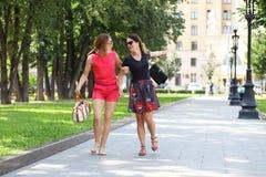 2 молодых счастливых женщины идя в город лета Стоковое Изображение