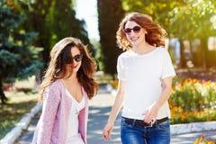 2 молодых счастливых женщины идя в город лета Стоковые Изображения