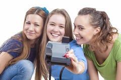 3 молодых счастливых кавказских женщины при Photocamera принимая собственную личность Стоковое Изображение