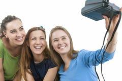 3 молодых счастливых кавказских женщины при Photocamera принимая собственную личность Стоковые Изображения RF
