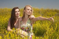 2 молодых счастливых друз распологая на траву и улыбку Стоковая Фотография