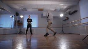 2 молодых танцора бедр-хмеля участвуя в сражении танца Подросток в черных брюках и пуловере наблюдая его друга видеоматериал