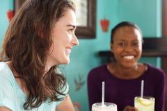 2 молодых усмехаясь женщины на кафе Стоковые Фотографии RF