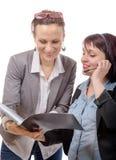 2 молодых усмехаясь женщины работая вместе с тетрадью стоковое изображение rf