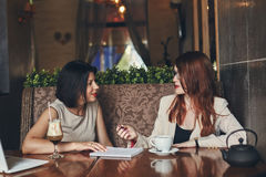 2 молодых усмехаясь кавказских коммерсантки с компьтер-книжкой Женщины в кафе Стоковые Фотографии RF