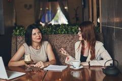 2 молодых усмехаясь кавказских коммерсантки с компьтер-книжкой Женщины в кафе Стоковое Изображение RF