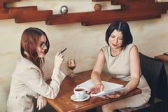 2 молодых усмехаясь кавказских коммерсантки с тетрадью Женщины в кафе Стоковые Фото
