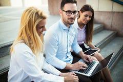 3 молодых усмехаясь коллеги работая совместно на компьтер-книжке Стоковые Фото