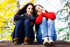 2 молодых усмехаясь друз сидя на лестницах Стоковое Изображение RF
