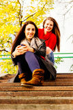 2 молодых усмехаясь друз сидя на лестницах Стоковое Фото