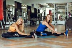 2 молодых худеньких белокурых женщины делая тренировки в спортзале Стоковые Изображения
